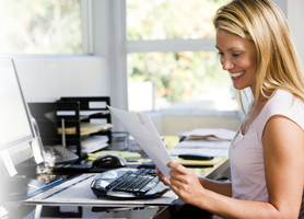 Woman at computer smiling at a piece of paper